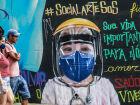 Pedestres caminham na frente de grafite em alusão ao surto do novo coronavírus na zona norte de São Paulo