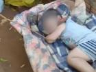 Criança de dois anos é vista deitada num colchão posto no chão