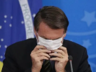 O presidente Jair Bolsonaro ajusta uma máscara no rosto