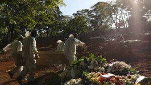 Coveiros usando roupas de proteção carregam um caixão no cemitério de Vila Formosa em São Paulo.