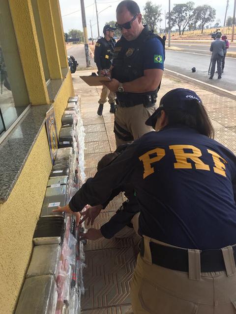 Policias rodoviários federais verificam e conferem a droga