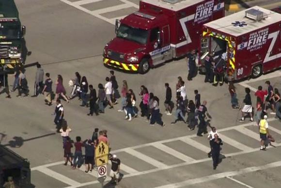 Students are evacuated from Marjory Stoneman Douglas High School during a shooting incident in Parkland, Florida, U.S. February 14, 2018