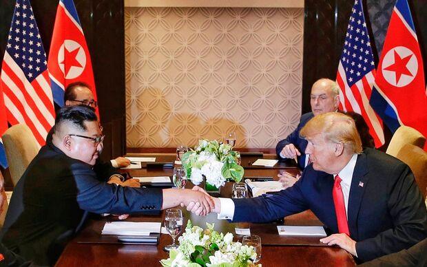 Kim Jong-Un e Donald Trump se cumprimentam durante reunião ao lado de assessores, em Singapura