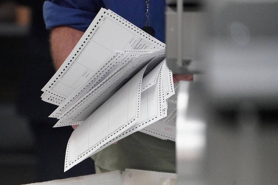 Funcionário da comissão eleitoral segura cédulas durante recontagem dos votos em Lauderhill, na Flóirda