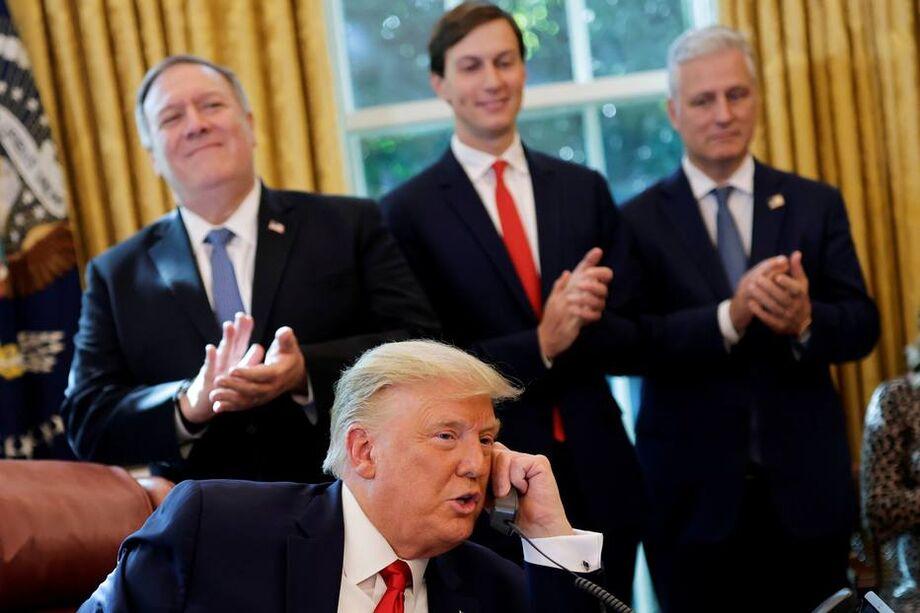Mike Pompeo (E) e Jared Kushner (D) aplaudem Donald Trump em conversa por telefone com líderes do Sudão e de Israel