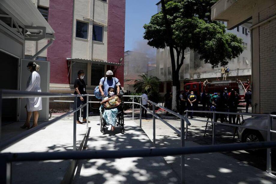 Paciente sendo retirada de cadeiras de rodas após incêndio que atingiu Hospital Federal de Bonsucesso