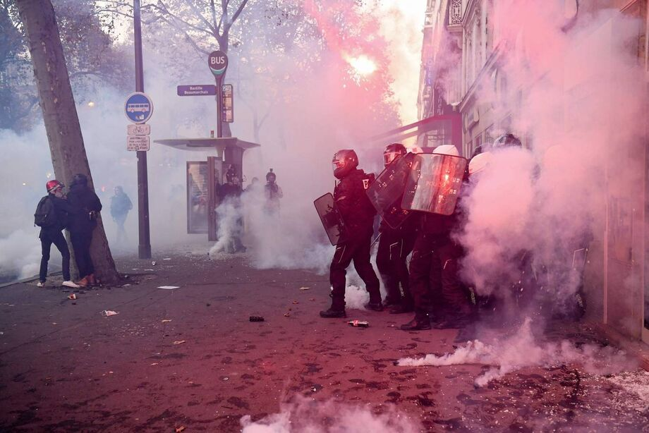 Policiais em meio à fumaça de bombas de gás durante confronto com manifestantes em Paris