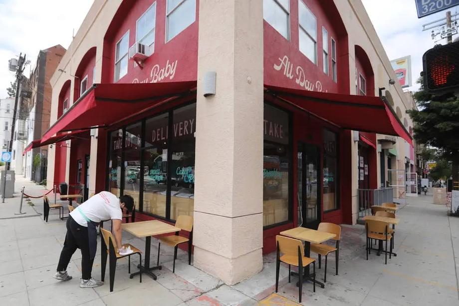 Funcionário de restaurante de Los Angeles, na Califórnia, higieniza assentos e mesas à espera de clientes