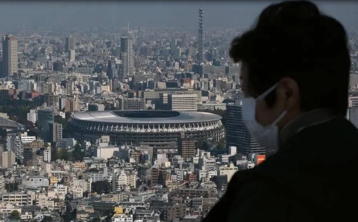 Homem observa o Estádio Nacional de Tóquio, principal palco dos Jogos Olímpícos de 2021