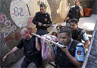 Policiais carregam corpo na favela Santo Amaro, onde houve tiroteio quarta-feira