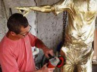 Ique, cartunista campo-grandense da TV Globo (RJ), retocando o bronze da escultura do João Saldanha