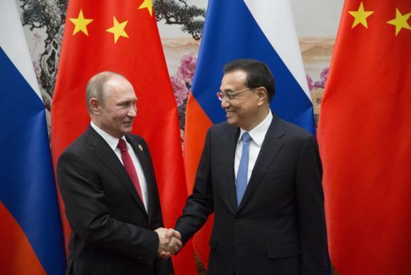 Presidente russo Vladimir Putin (E) cumprimenta o premier chinês Li Keqiang durante o fórum em Pequim
