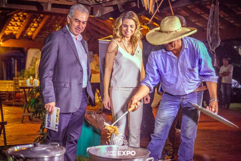 A anfitriã do evento, Alessandra Piano, mostra ao Governador Reinaldo Azambuja, uma das atrações comida tipicamente pantaneira