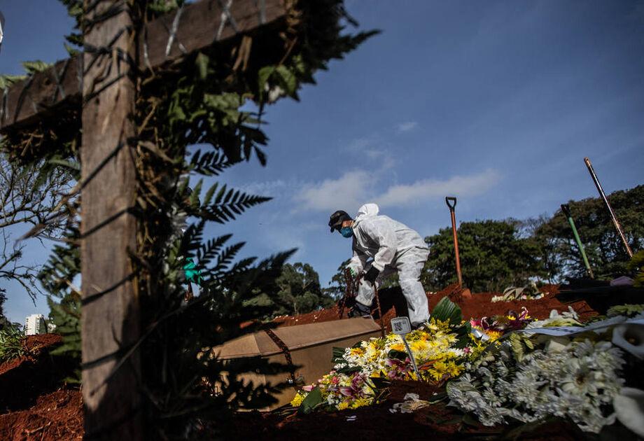 Funcionários vestidos com roupas de proteção fazem o sepultamento de vítimas do novo coronavírus no Cemitério da Vila Formosa, na zona leste da capital paulista
