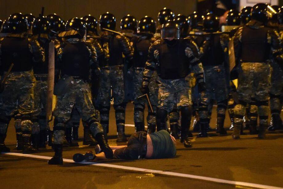 Barreira policial passa por homem caído no chão durante protestos da oposição na Bielo-Rússia