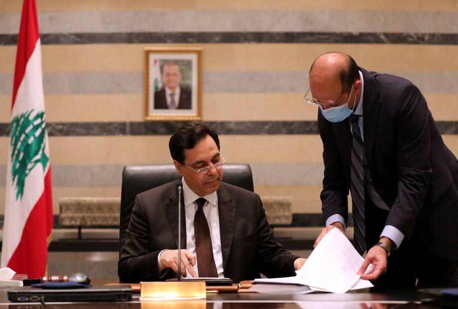 O ministro da saúde do Líbano (em pé) conversa com o primeiro-ministro Hassan Diab