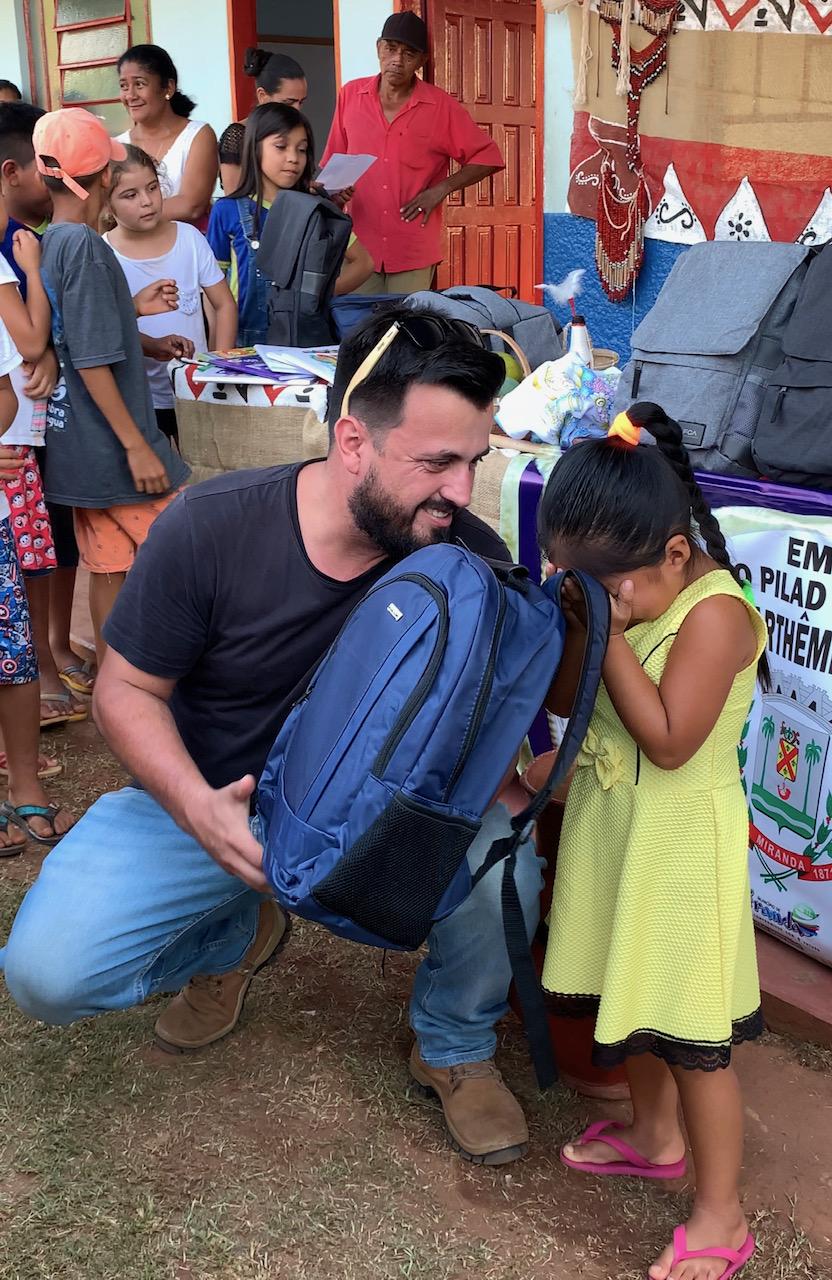 O jornalista Leandro Gameiro realiza entrega simbolica de um Kit Escolar para uma das alunas da escola